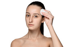 Skin care woman removing face with cotton swab pad. Skin care concept. Facial closeup of beautiful Caucasian model with perfect skin. Girl isolated on white Royalty Free Stock Image