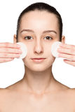 Skin care woman removing face with cotton swabs. Skin care concept. Facial closeup of beautiful Caucasian model with perfect skin. Girl isolated on white Stock Photography