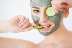 Skin Care. Young woman with cosmetic clay mask holding cucumber. At her bathroom stock photos