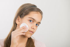 Skin cleansing. Teen girl holds cotton pad near the face. teen cleansing, beautiful girl holding a cotton ball near the face stock photography