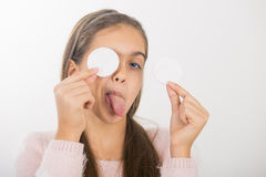 Skin cleansing. Teen girl holds cotton pad near the face. teen cleansing, beautiful girl holding a cotton ball near the face royalty free stock photos