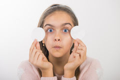 Skin cleansing. Teen girl holds cotton pad near the face. teen cleansing, beautiful girl holding a cotton ball near the face royalty free stock images