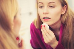 Woman using cotton pad to remove make up. Skin complexion care concept. Young woman using cotton pad to remove make up or dirt from face Royalty Free Stock Image