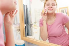 Woman using cotton pad to remove make up. Skin complexion care concept. Young woman using cotton pad to remove make up or dirt from face Royalty Free Stock Photography