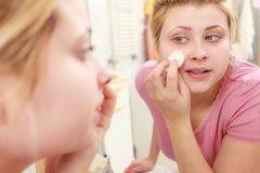 Woman using cotton pad to remove make up. Skin complexion care concept. Young woman using cotton pad to remove make up or dirt from face Royalty Free Stock Photos