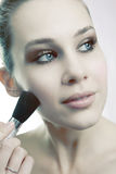 Skin cosmetics - woman using brush on her face Stock Photography