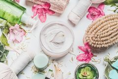 Skin cream with flowers petals and others body care cosmetic products and accessories on white background. Top view stock photo