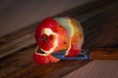 Skin peeled apple. Peeler skinning apple over wooden plank Royalty Free Stock Image