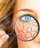 Skin problems. Abstract face of a woman with cracks and magnifying glass Royalty Free Stock Photography