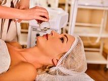 Skin resurfacing procedure facial procedure on ultrasound face machine. Female acne treatment. Woman receiving electric lift massage at spa salon. Modern Stock Photo