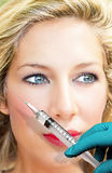 Skin Therapy. Face of a beautiful woman with doctors hand and syringe Stock Photos