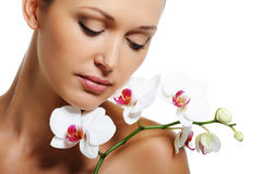 Skin treatment for beauty adult woman. Face of pretty beautiful woman with a white orchid on her shoulder Stock Photos