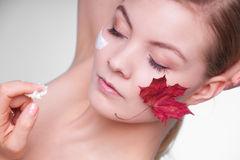Skin. young woman girl with red leaf and cream Stock Photography
