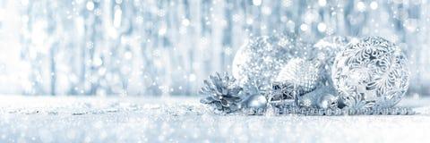 Skinande försilvra närvarande för jul och härliga prydnader, med defocused julljus i bakgrunden royaltyfri foto