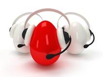 Skinande ägg med hörlurar med mikrofon över vit Arkivbild
