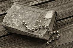 Skinande Glass pärlor som ligger på den sjaskiga slog gamla boken som ligger på royaltyfria bilder