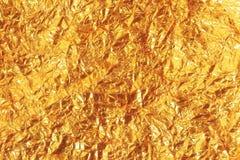 Skinande gul bakgrund för textur för guld- folie för blad fotografering för bildbyråer