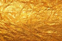 Skinande gul bakgrund för textur för guld- folie för blad royaltyfri foto