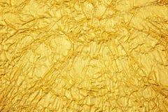 Skinande gul bakgrund för textur för guld- folie för blad arkivbilder