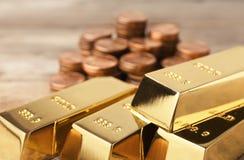 Skinande guld- stänger och mynt på tabellen arkivfoto