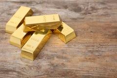 Skinande guld- stänger på trätabellen