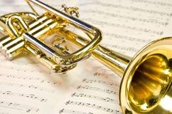 Skinande guld- trumpet som ligger på notblad royaltyfri foto