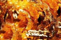 Skinande guling och orange guld- folie, abstrakt texturbakgrund Arkivfoto