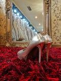 Skinande hög-heeled skostilett för silver på röd matta i bröllop Fotografering för Bildbyråer