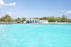 Skinande havsvatten med solljus och hus royaltyfri fotografi