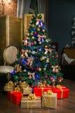 Skinande julgran som dekoreras med bollar och pilbågar, med gåvor under den i vind-stil vardagsrum bakgrund undersöker år för toy fotografering för bildbyråer