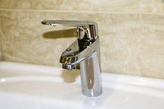 Skinande krom pläterade vattenkranen i badrum, med vattendroppar arkivfoto