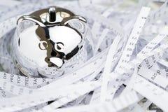 Skinande metallisk spargris i pappersredet som byggs från den finansiella rapporten som förstörs av metaforen för pappers- dokume royaltyfri fotografi