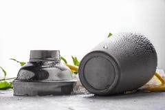 Skinande metallshaker på en grå bakgrund Öppnad grå behållare på en grå tabell En krus för framställning av coctailar Arkivbild