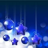 Skinande prydnader och ljus på blå bakgrund för helig jul Royaltyfria Bilder