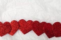Skinande röda hjärtor på vitbok Arkivfoton