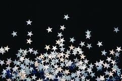 Skinande stjärnor av folie på svart bakgrund festliga konfettiar royaltyfria bilder