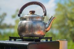 Skinande tekanna med ett trähandtag på gasugnen, på campingplatsen för en picknick Arkivbild