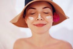 应用在面孔的妇女微笑防晒霜 Skincare 身体太阳保护 遮光剂 帽子污迹润湿的化妆水的女性在滑雪 免版税库存照片