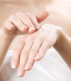 Skincare. Female applying moisturizer to her Hands after bath Royalty Free Stock Photos