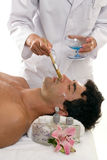 Skincare. A woman applies a purifying mask to a male customer's face Stock Photography
