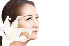 Skincare av den unga härliga kvinnaframsidan med isolaten för ny blomma Royaltyfri Fotografi