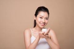 Skincare. Beautiful asian woman show moisturizer or lotion produ. Ct Royalty Free Stock Photo