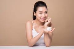 Skincare. Beautiful asian woman show moisturizer or lotion produ. Ct Stock Photo