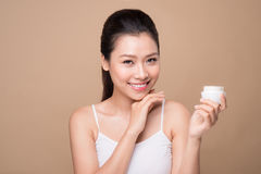 Skincare. Beautiful asian woman show moisturizer or lotion produ. Ct Royalty Free Stock Photography
