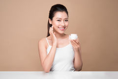 Skincare. Beautiful asian woman show moisturizer or lotion produ Royalty Free Stock Photo