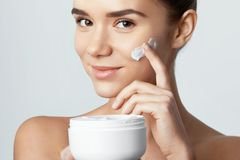 Skincare. Beauty Concept. Young pretty woman holding cosmetic cream.  royalty free stock images