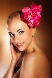 Schönes Gesicht der jungen Frau der Nahaufnahme mit Blume. Mädchenlächeln. Stockfotos