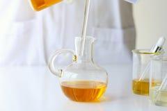 Skincare för vetenskaper för skönhetskönhetsmedel för formulera och blandnings, med växt- extrakt, forskare som häller organisk n Royaltyfri Bild