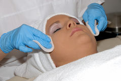 Skincare facial treatment at day spa. Being preformed on face of woman wrapped in a towel Stock Images