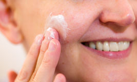 Skincare. Mature woman spreading skincare cream on her cheek, horizon format Royalty Free Stock Images